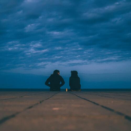 girl and guy sitting on dock